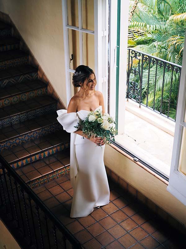 bride waiting to walk down isle by window