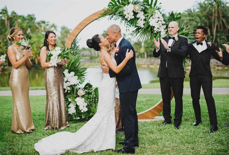 bride and groom having their first kiss at alter