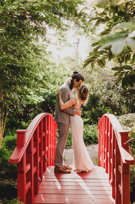 bride and groom kissing on small red bridge