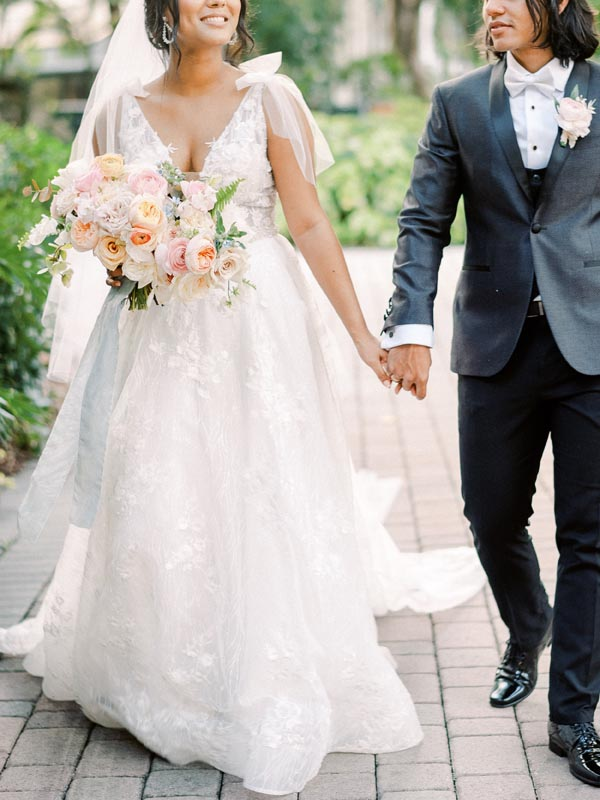 bride and groom walking outside hand in hand