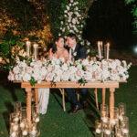 bride and groom sitting behind flower arrangement