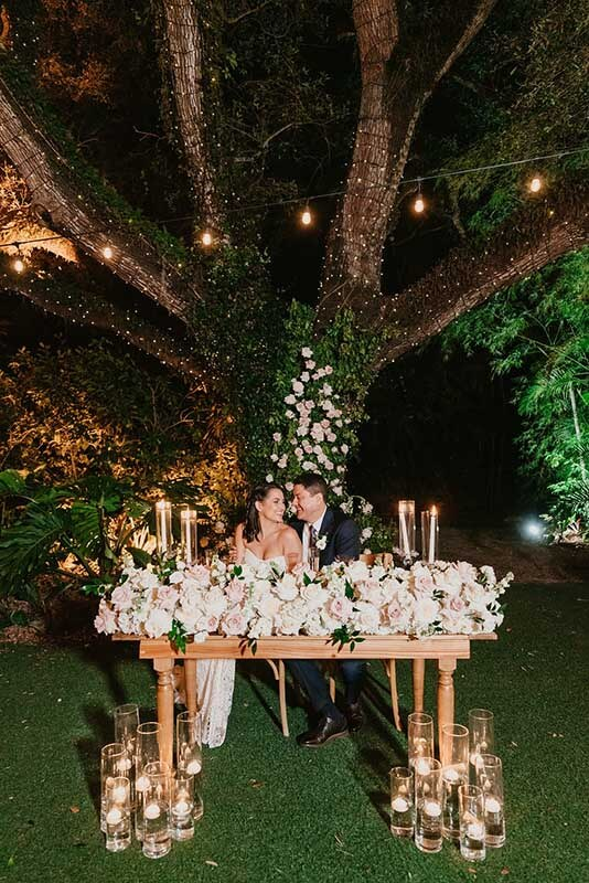 bride and groom at table and lots of flowers