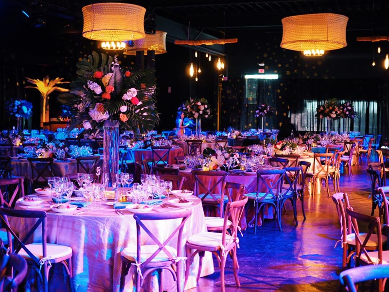 large wedding reception venue with round tables and tropical theme