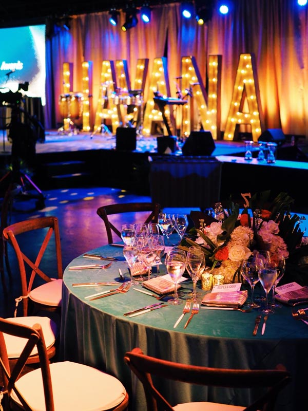 large Havana letters on stage behind instruments with table setting for guests at wedding reception