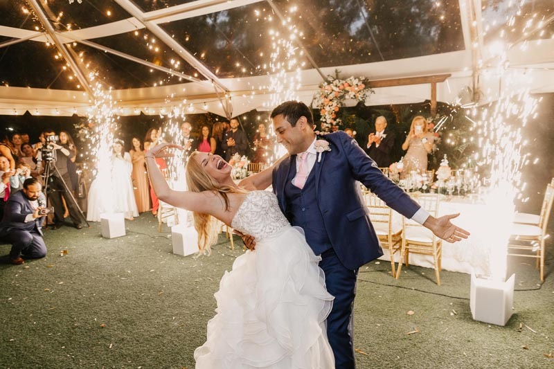 groom dipping his wife for flashy photo with fireworks