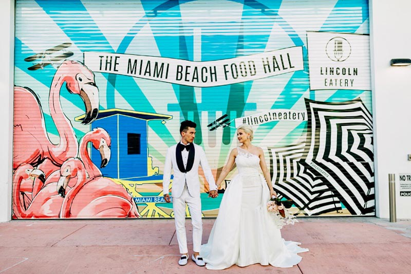 wedding photo of bride and groom both in white with garage in background that has the miami beach food hall text on it