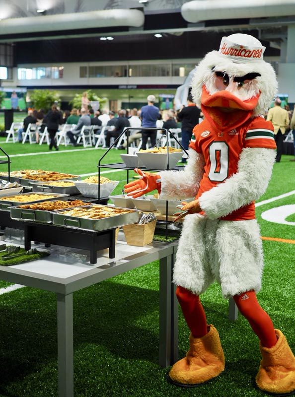 Hurricanes mascot posing with catering display