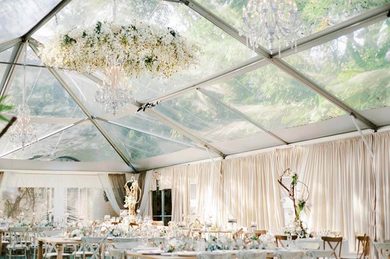 wedding reception venue outdoors under tent with clear roof