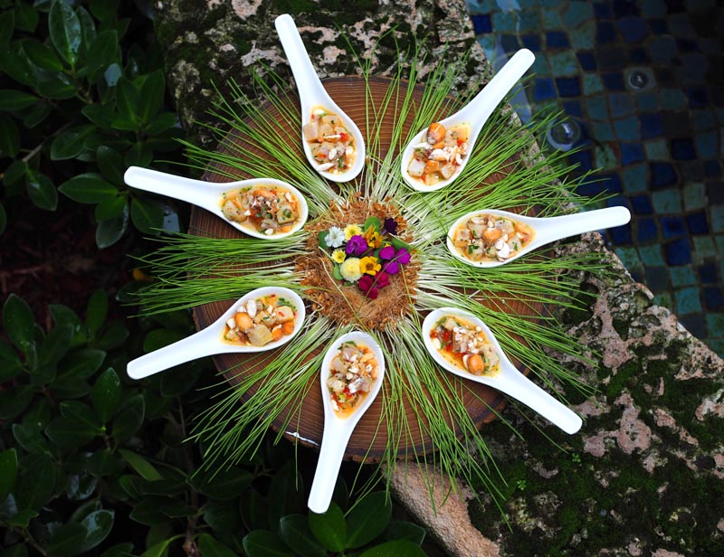 large serving spoons with appetizers displayed on wood disc