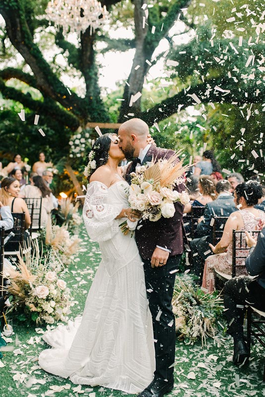 bride and groom kissing at the end of the isle